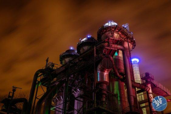 Fotografie van de kleurrijk verlichte gebouwen van het landschaftpark in Duitsland bij avondlicht.