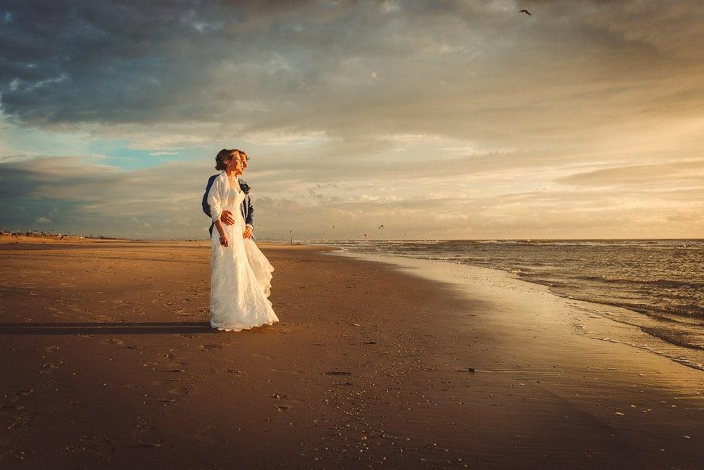 Fotografie van bruidspaar op het strand van Scheveningen na een storm, gemaakt door De Bruiloftfotograaf.