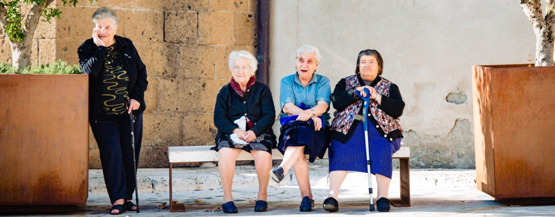 4 oudere vrouwen op een pleintje in Toscane