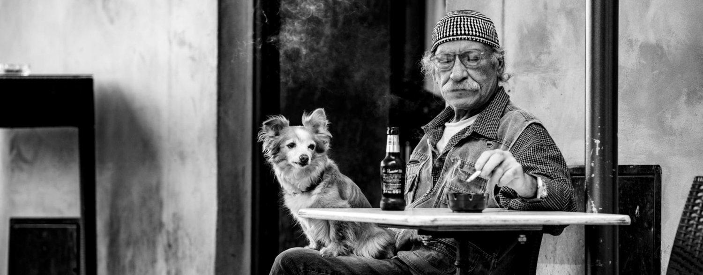 Oude man met hond op terras in Toscane